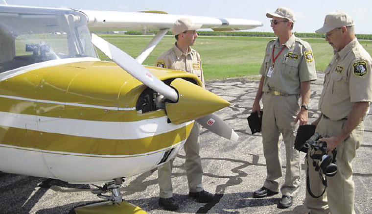 (L to R):  Deputies Darrell Witham, Norm Hurren, Don Johnston standing by Darrell's plane.