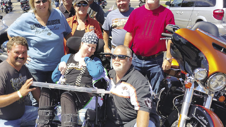Participants in the annual Hog Town Run took time Saturday for a picture with fellow bikers Dale Simpson (kneeling front row at right) and his wife, Beth Ann. The Marlette couple used to enjoy riding motorcycles, until her accident 13 years ago.