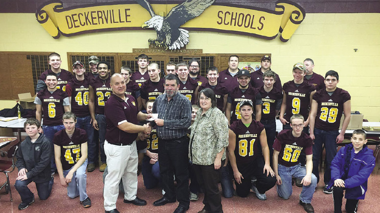 Coach Bill Brown and the football team presented Bob and Bonnie Wolf with a check for Relay for Life.