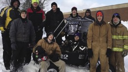 The Engineering and Design SAE Baja Team stand proudly next to their race vehicle.